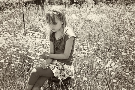 young girl on wooden barrel in wild daisy field