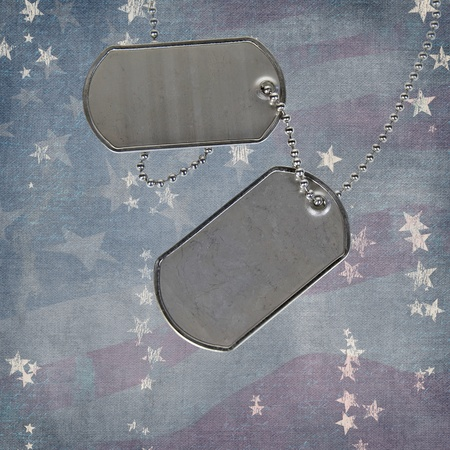 Military dog tags on faded textured flag background.