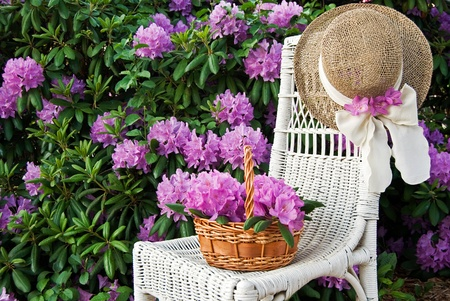 Flower basket on white wicker chair with hat.