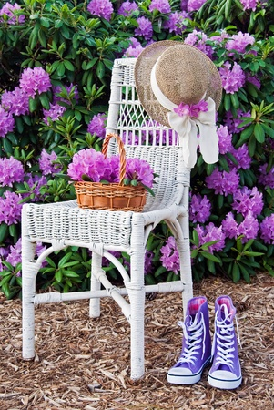 Wicker chair in azalea garden with sneakers and hat.