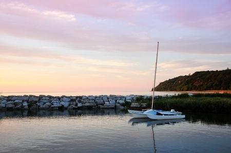 pink cruiser: Catamaran in cove at sunset.