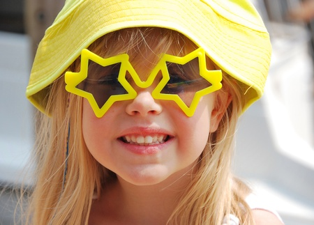 little blond girl with yellow hat and star sunglasses