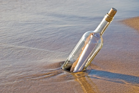 message bottle: Message in a bottle stuck in beach sand.