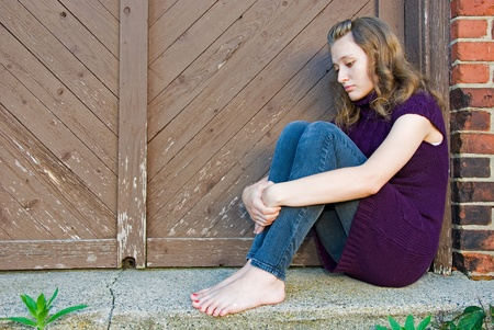 barefoot people: teenage girl huddled in old doorway Stock Photo