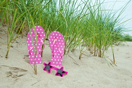 star sunglasses and flip-flops in beach sand photo