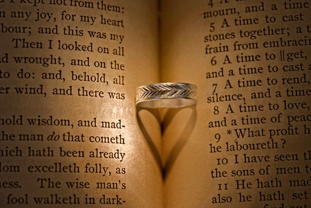 platinum: wedding ring creating a shadow in vintage Bible