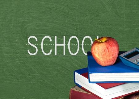 apple on school books with green chalkboard