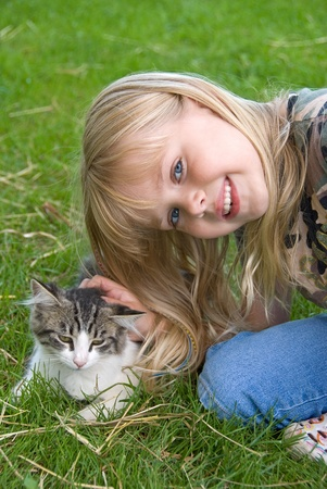 little girl petting kitten photo