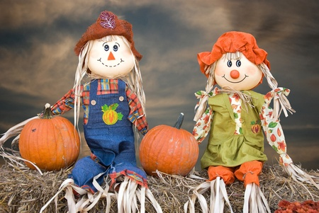 scarecrow couple with pumpkins on hay bales