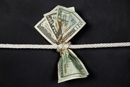 протяжение: деньги связаны в узел Фото со стока
