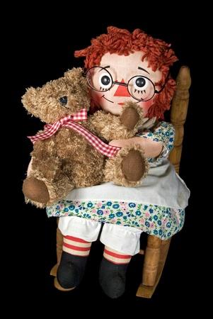 Rag doll and teddy bear in rocking chair.