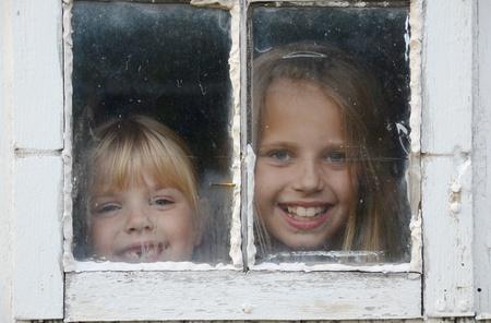 pane: little girls peeking in old barn window