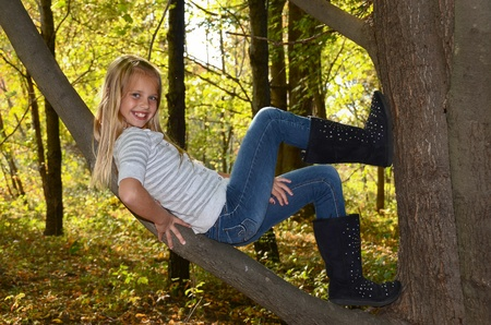 young girl reclining on tree limb photo