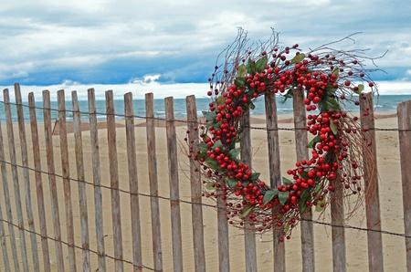 Berry wreath on beach fence. Stock Photo