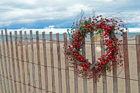 Christmas wreath with starfish on beach fence.