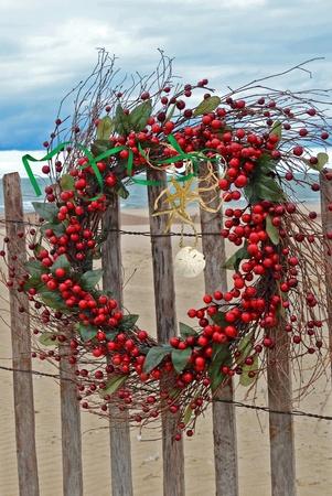 Christmas berry wreath on beach fence.