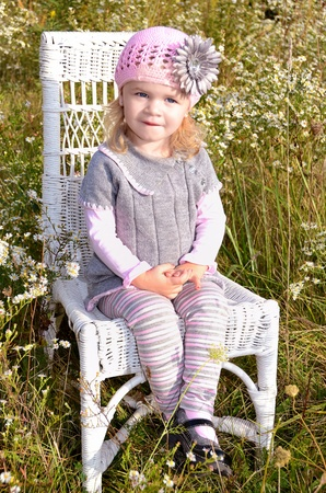 Little girl sitting pretty on a wicker chair. photo