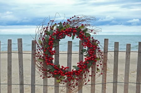 Holiday berry wreath on beach fence.