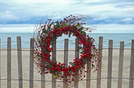 christmas berries: Vacanze sulla corona di bacche recinzione spiaggia. Archivio Fotografico