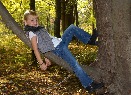 Blond little girl leaning on tree limb. photo