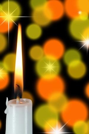 white candle burning on bokeh background