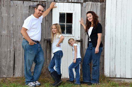American family posing by old barn.