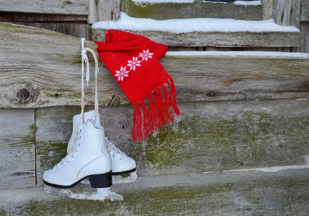 old barn in winter: ice skates with scarf hangin on barn