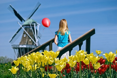 dutch girl: girl with red balloon in Dutch spring garden Stock Photo