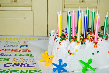 jacks: Unlit birthday candles in cake with toy jacks