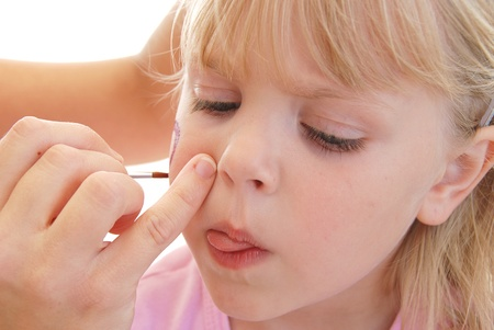 pinkie: Little girl getting her cheek painted  Stock Photo