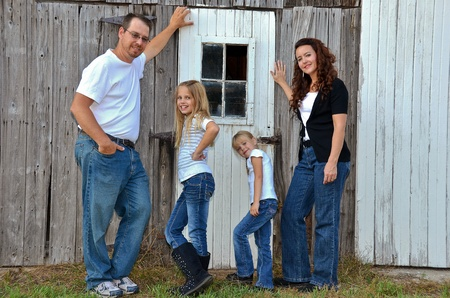 barn girls: American family posing by an old barn