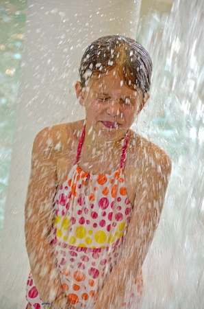 cascade: Girl in polka dot swimsuit getting splashed  Stock Photo