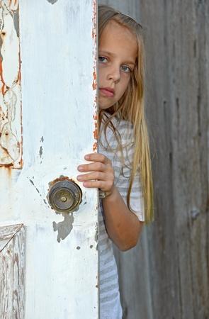 door knob: Young girl peeking around old door