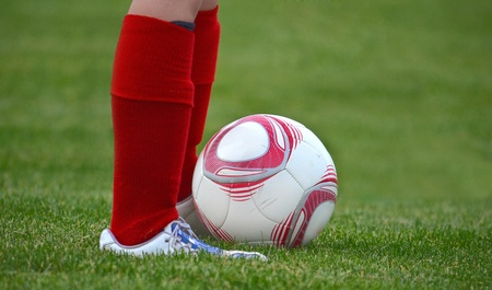 young soccer player standing by ball