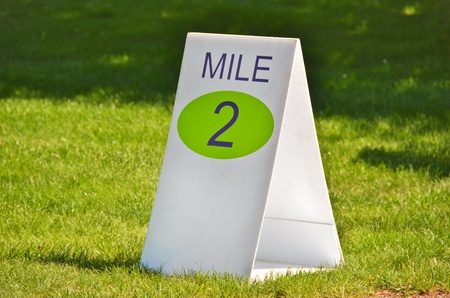 mile: mile marker sign in grass for race