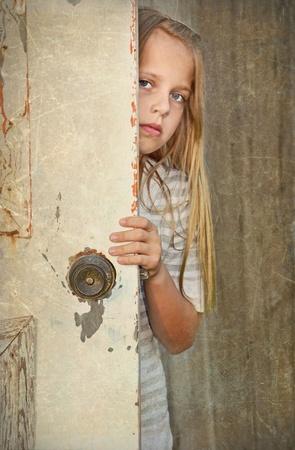 girl looking around old door photo