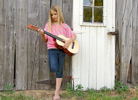 young blond girl playing guitar by old barn photo
