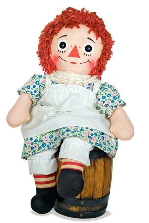 old rag doll on wooden barrel Standard-Bild