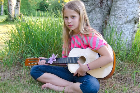 girl with guitar outdoors photo