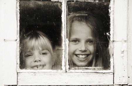 little girls peeking out of grungy window photo