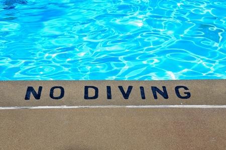 no swimming: warning sign at edge of swimming pool
