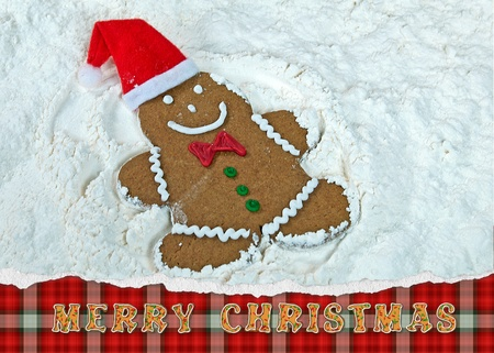 gingerbread cookie making a snow angel in flour photo