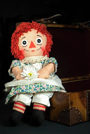 old rag doll sitting on a suitcase