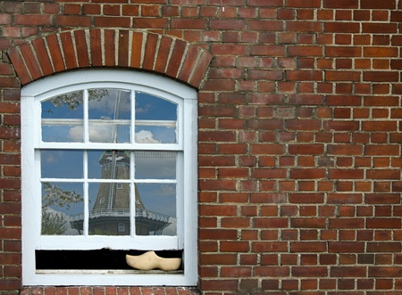 wooden shoe in window with windmill reflection