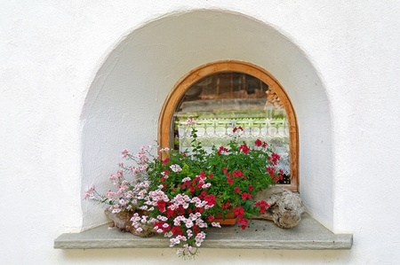 old-fashioned arched window with geraniums