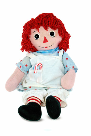 old rag doll with candy cane isolated on white