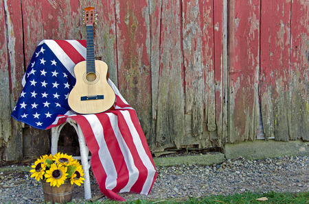 red chair: guitar on American flag by old barn