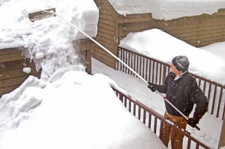 man met behulp van sneeuw rake om sneeuw van het dak te verwijderen
