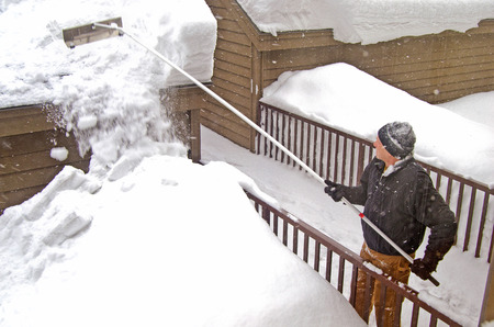 man using snow rake to remove snow from roof