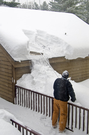 man removing snow from garage roof Standard-Bild